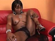 Black tattooed shemale jerks off on red leather couch