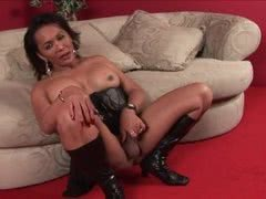 Mature shemale Leah masturbates in her black leather boots