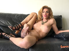 Busty TS bimbo Jenna Tales jerk of on her leather couch