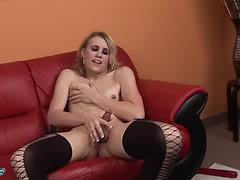 Blonde shemale jerks off in black fishnet stockings
