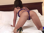 Shemale with purple lingerie and black heels shows her ass
