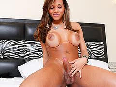 Cute tranny in fetish gear plays with her dick