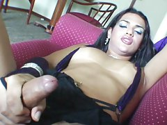 Tgirl on the couch leans back to stroke