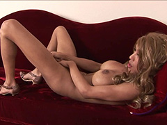Busty american tgirl masturbating on red sofa