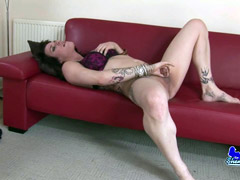 Hung shemale playing her cock on red sofa